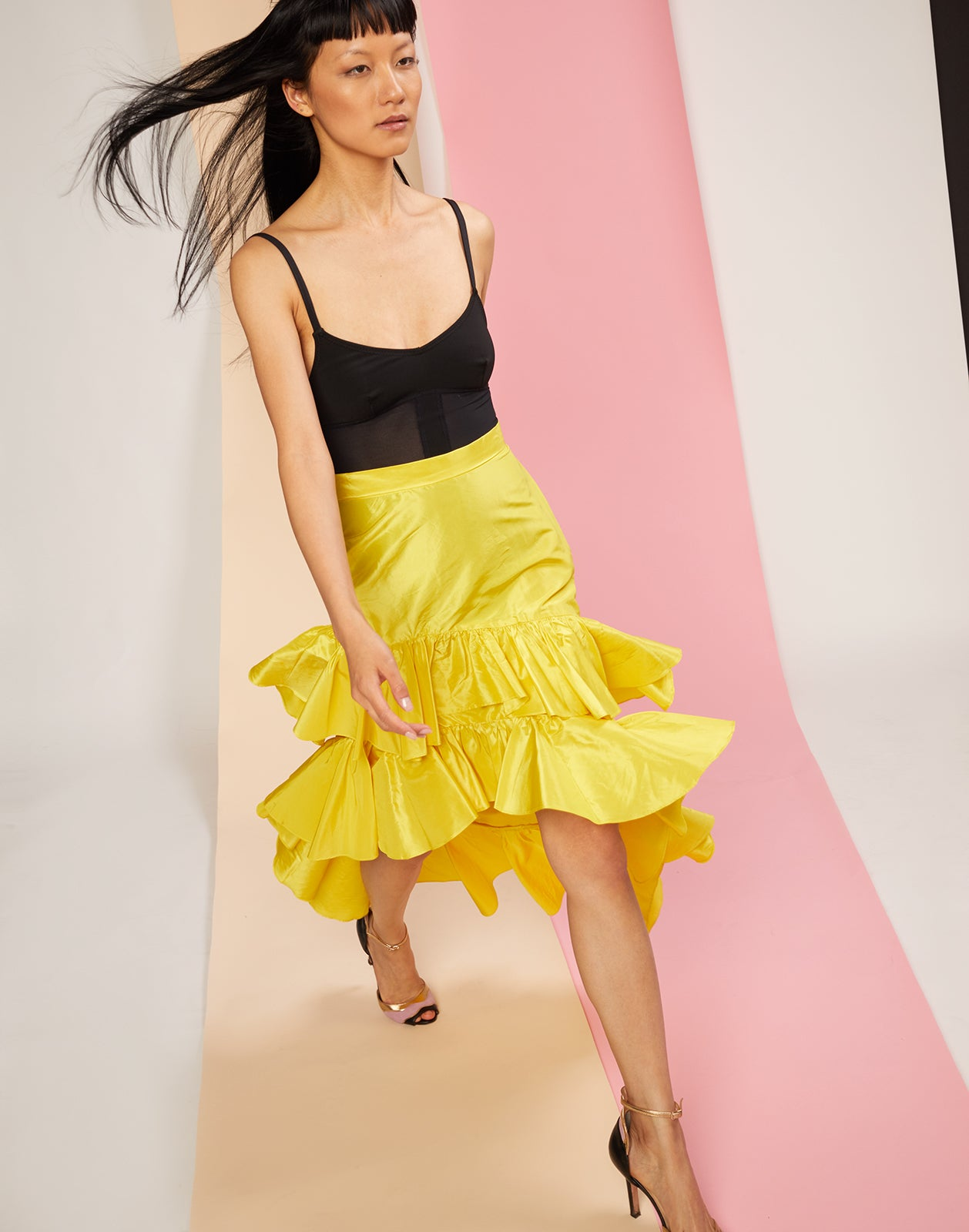 Model walking in yellow silk taffeta skirt with asymmetrical cascading ruffles.