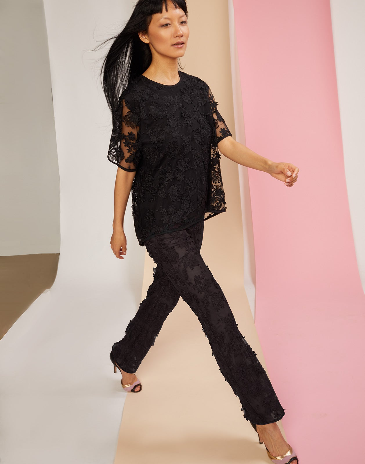 Model walking in the black Crossfade lace pant and tee set.