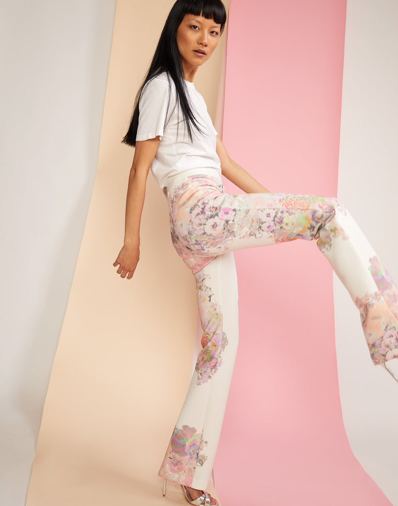 Side view with model posing with leg up in floral printed flares in sleek bonded nylon