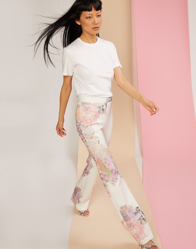 Diagonal walking shot of floral printed flare pants in sleek bonded nylon