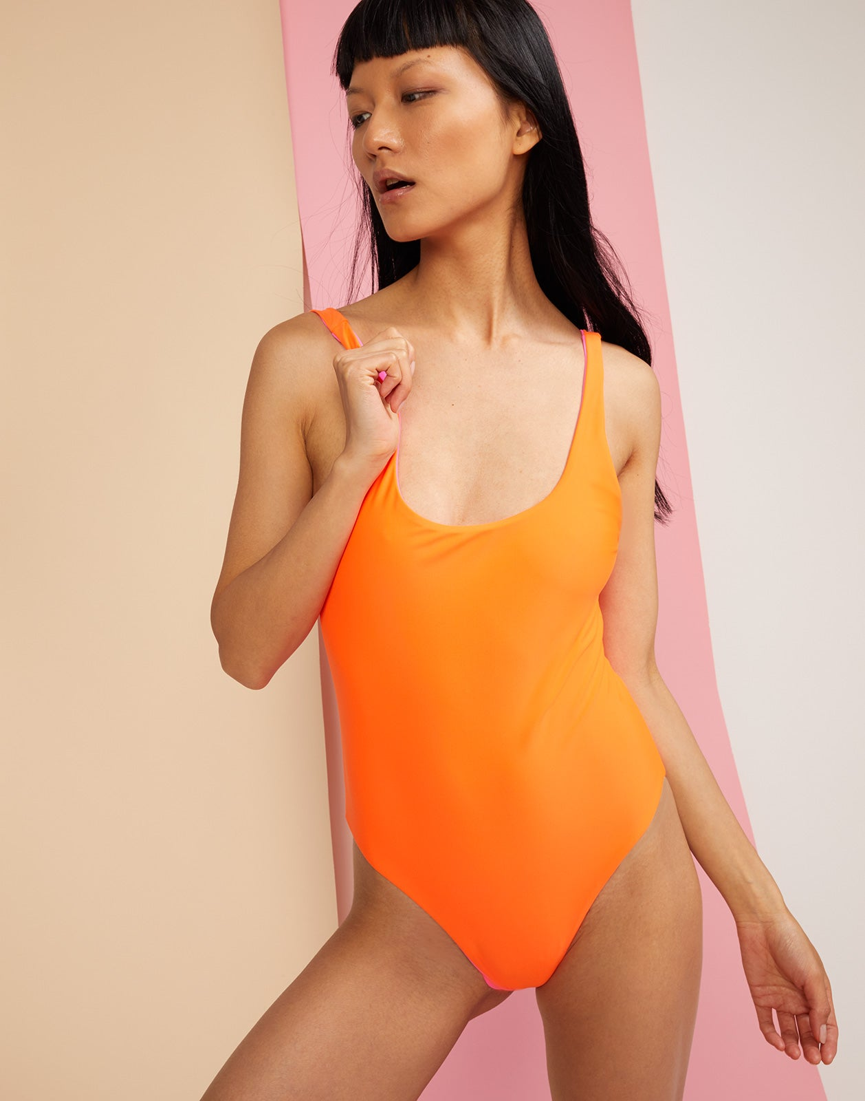 Front view of reversible swimsuit with 'lovedove' embroidery worn on orange side.
