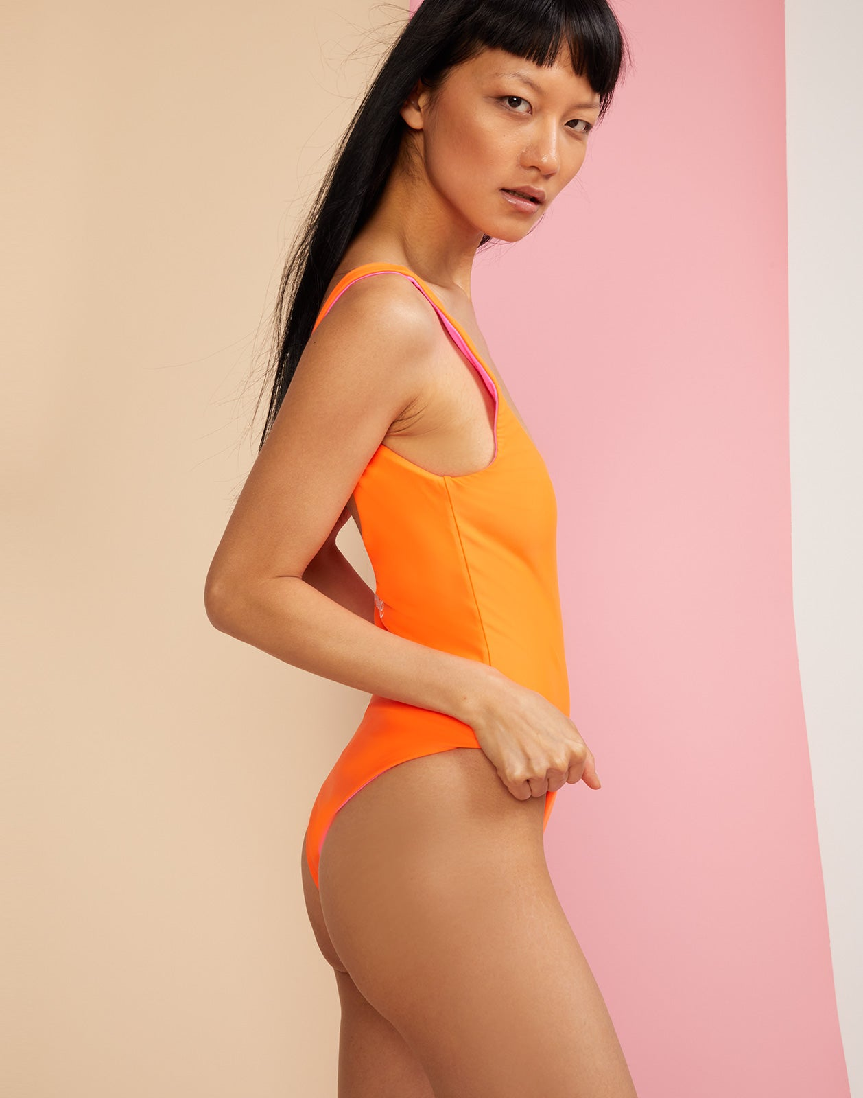 Side view of 'lovedove' swimsuit on orange side.