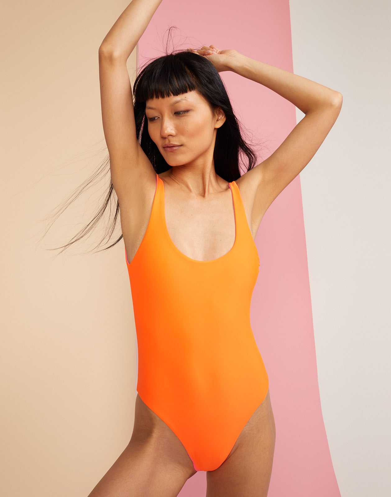 Front view of reversible swimsuit with 'lovedove' embroidery in orange
