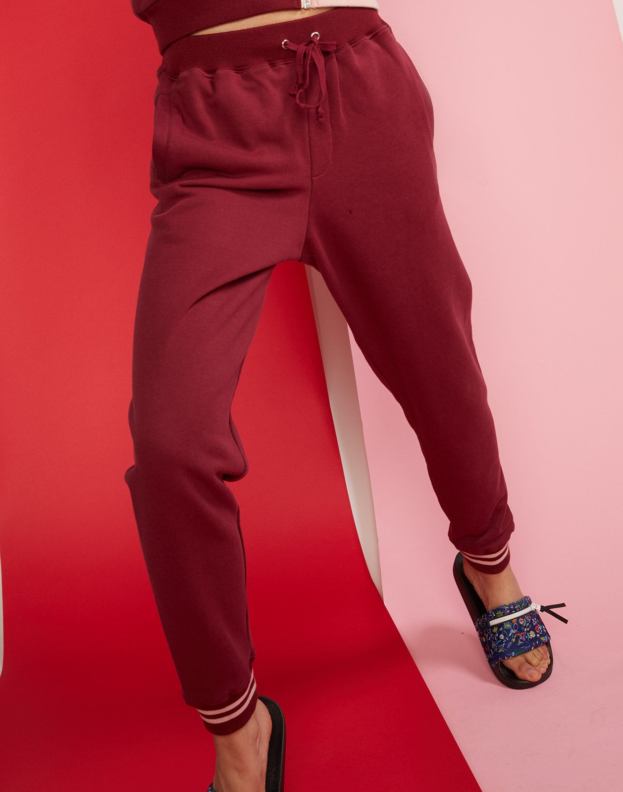 Close detail view of burgundy cotton jogger sweatpants with drawstring waist.