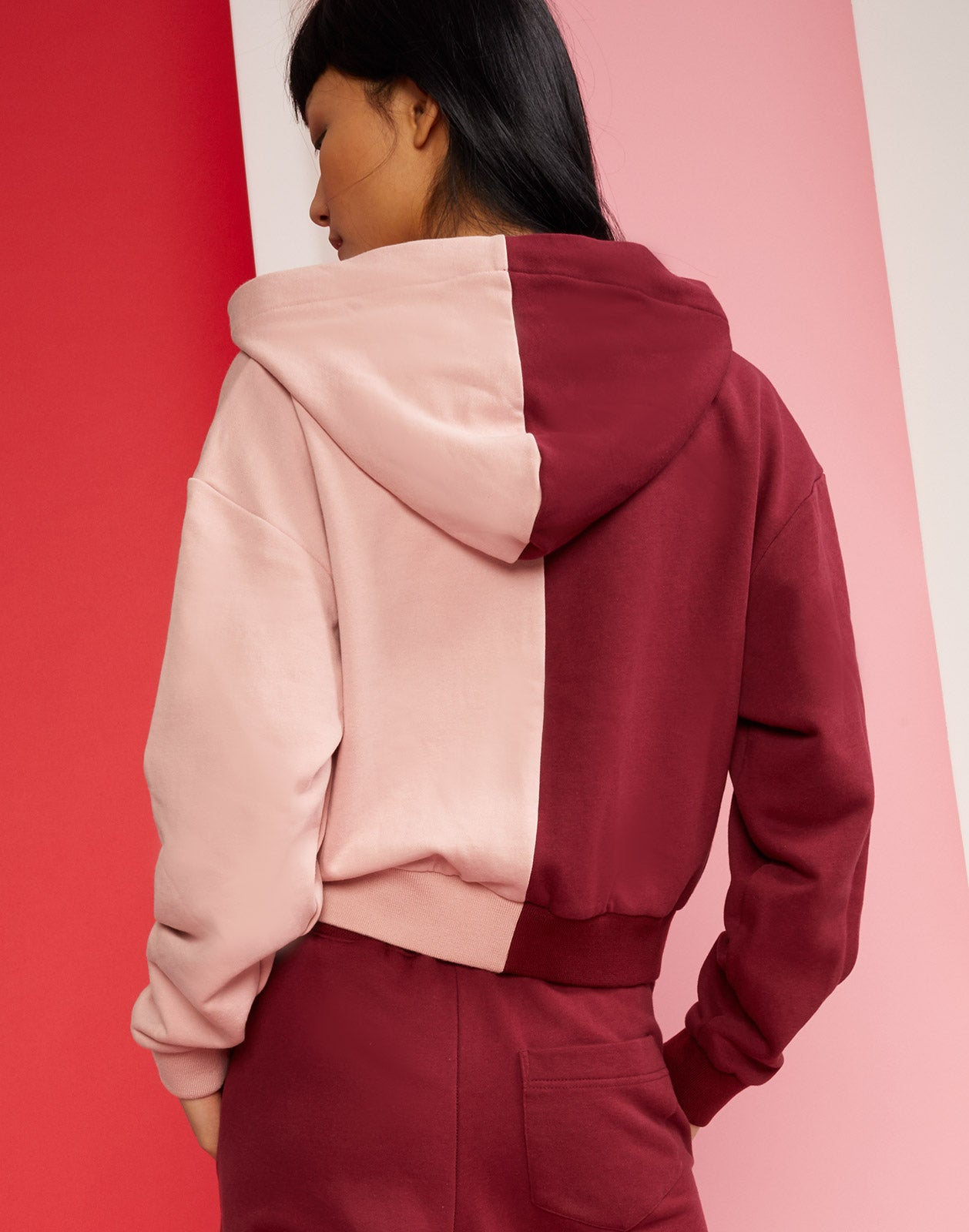 Back view of CaliYork Sweatshirt with hood in two-tone burgundy and blush design.
