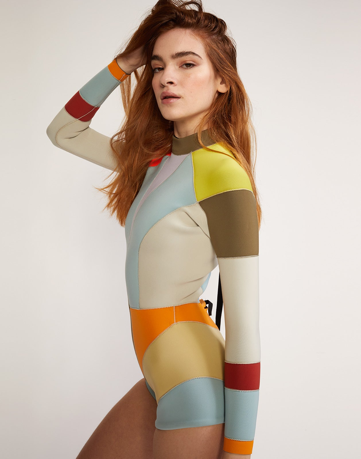 Side view of multi-color asymmetrical colorblock full performance wetsuit.