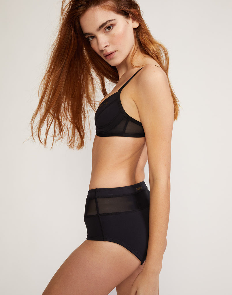 Side view of high waisted neoprene bikini bottom with sheer mesh inserts.