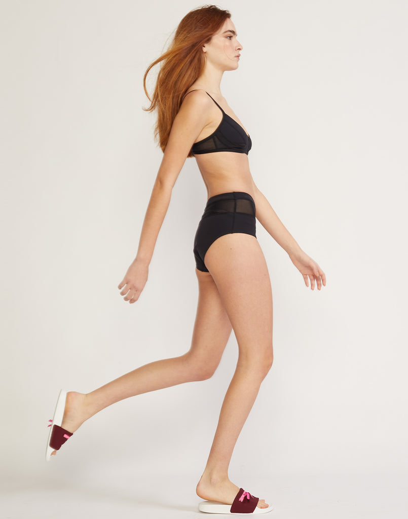 Full length side view of high waisted neoprene bikini bottom with sheer mesh inserts.