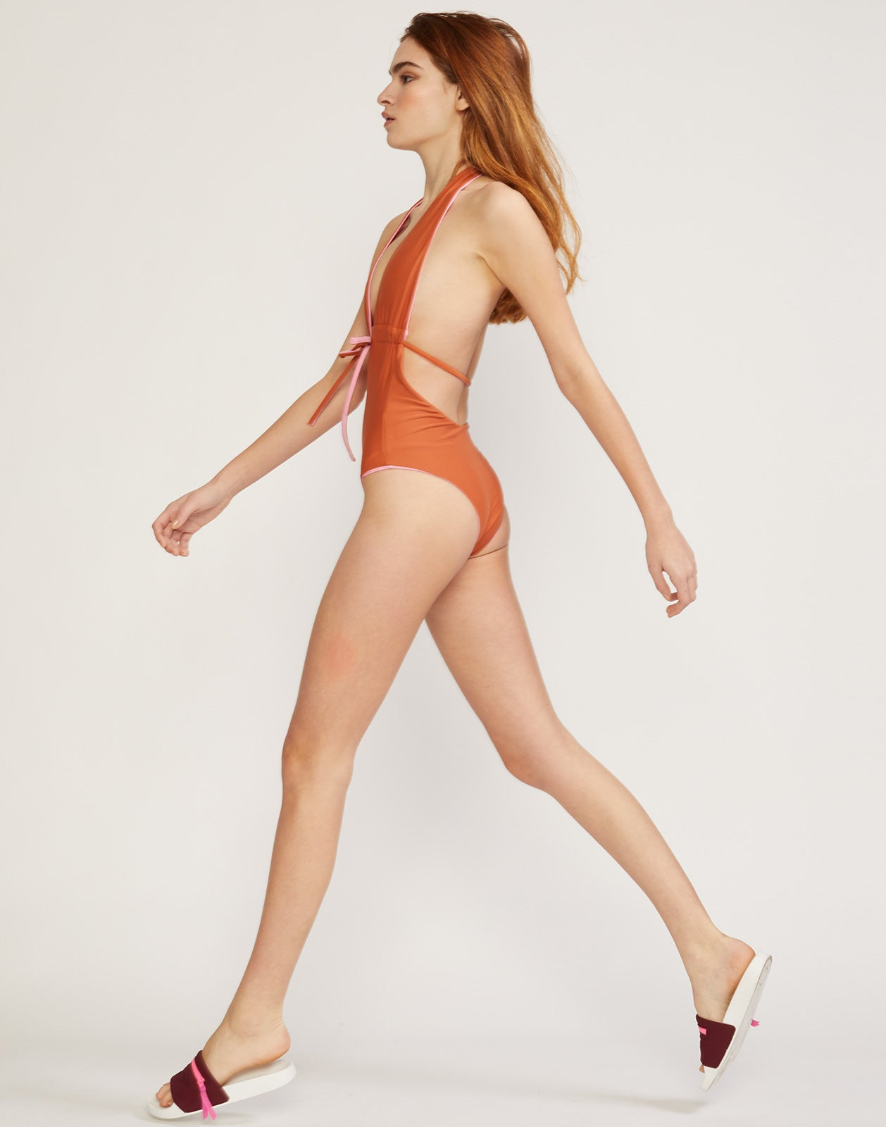 Side view of model walking in the halter-neck Heartbreakers Reversible One Piece swimsuit.