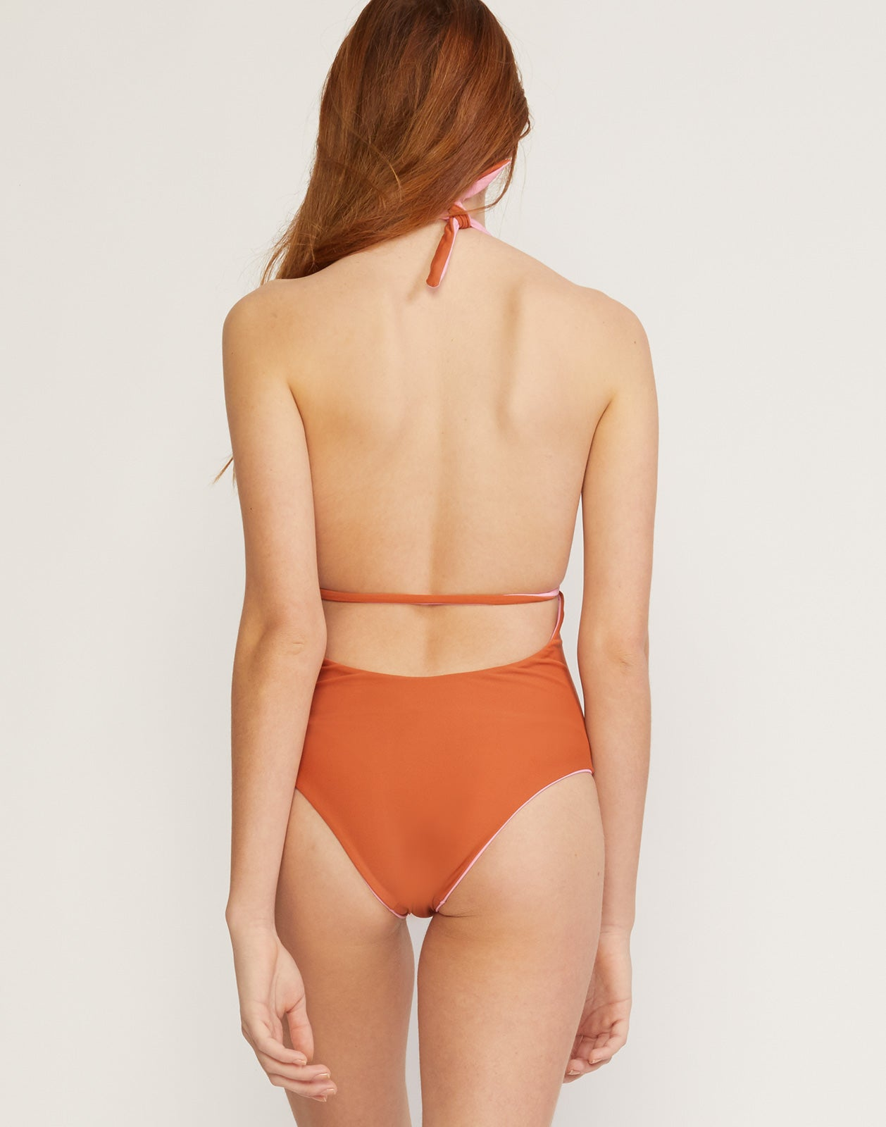Back view of the Heartbreakers reversible one piece swimsuit in copper and blush.