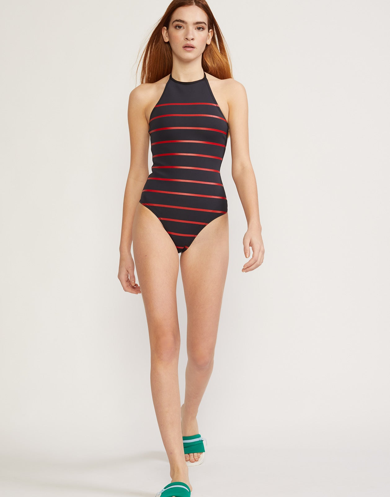 Full length view of model walking in red and navy striped neoprene one piece swimsuit with halter neck.