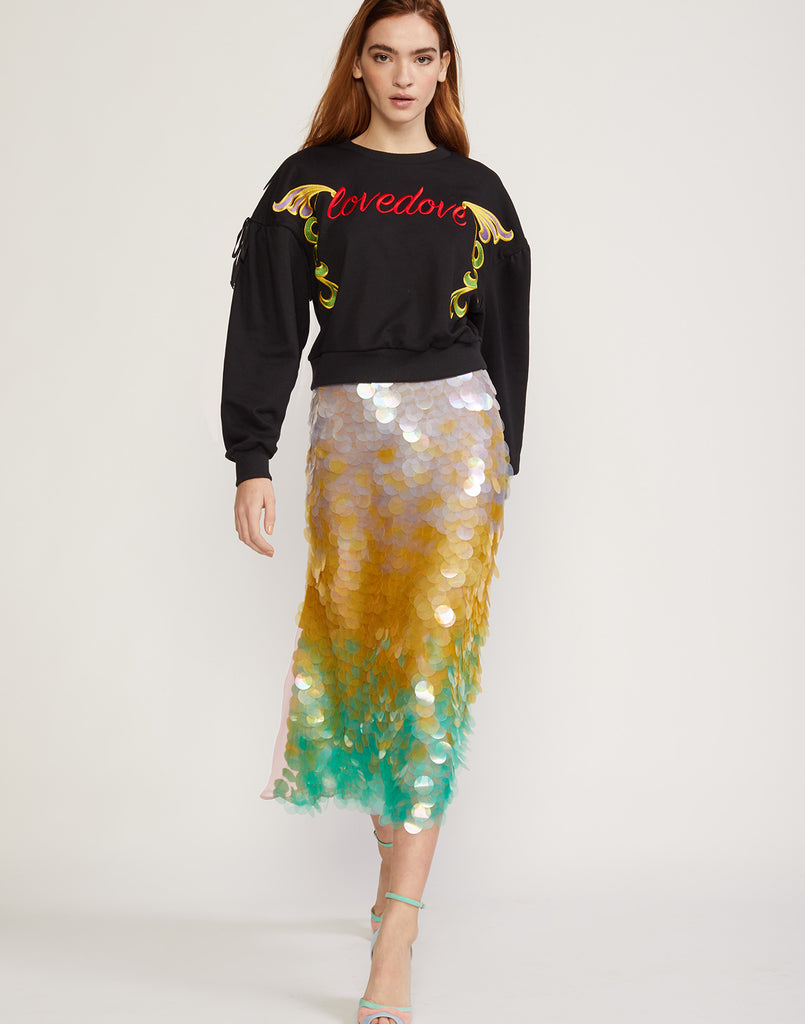 Front view of model walking in iridescent sequin skirt with ombre cascading pailletes.