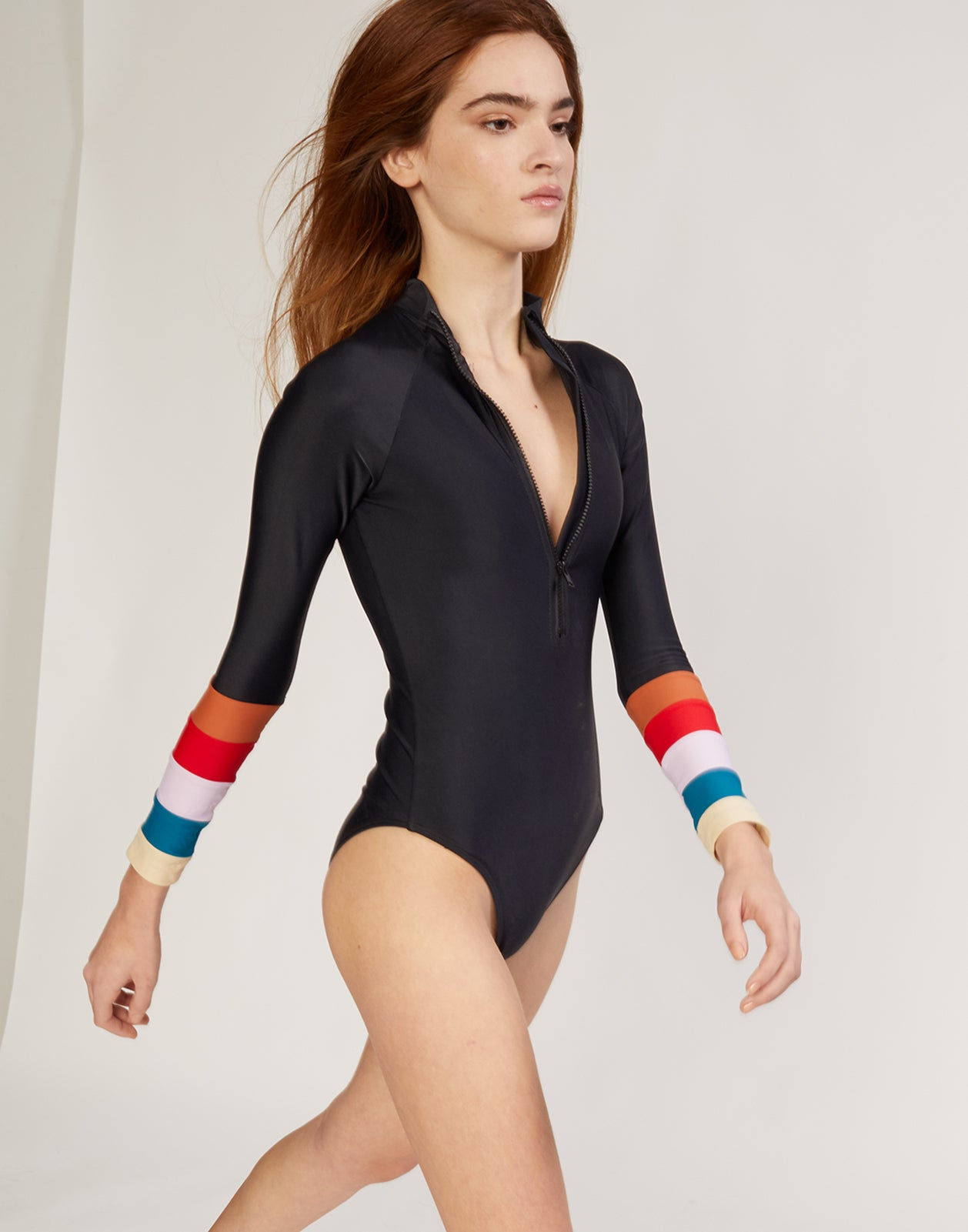 Side view of surf suit with colorblock striped sleeves and front zipper.