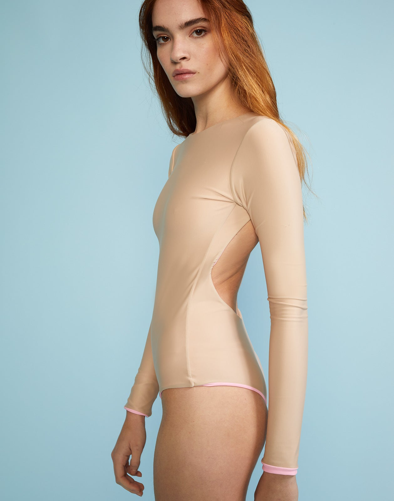 Side view of solid two-tone surf suit with open back.