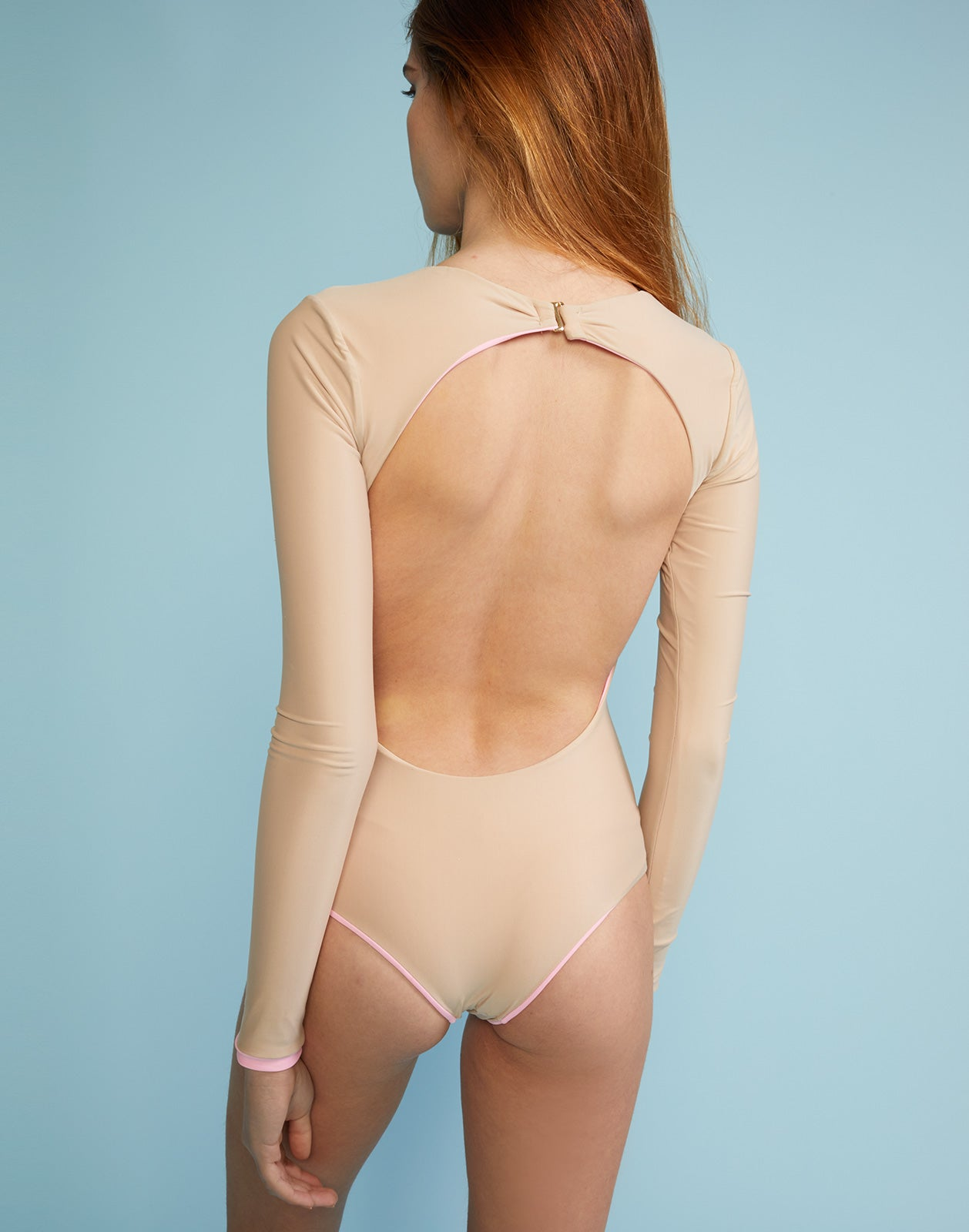 Back view of solid two-tone surf suit with open back.