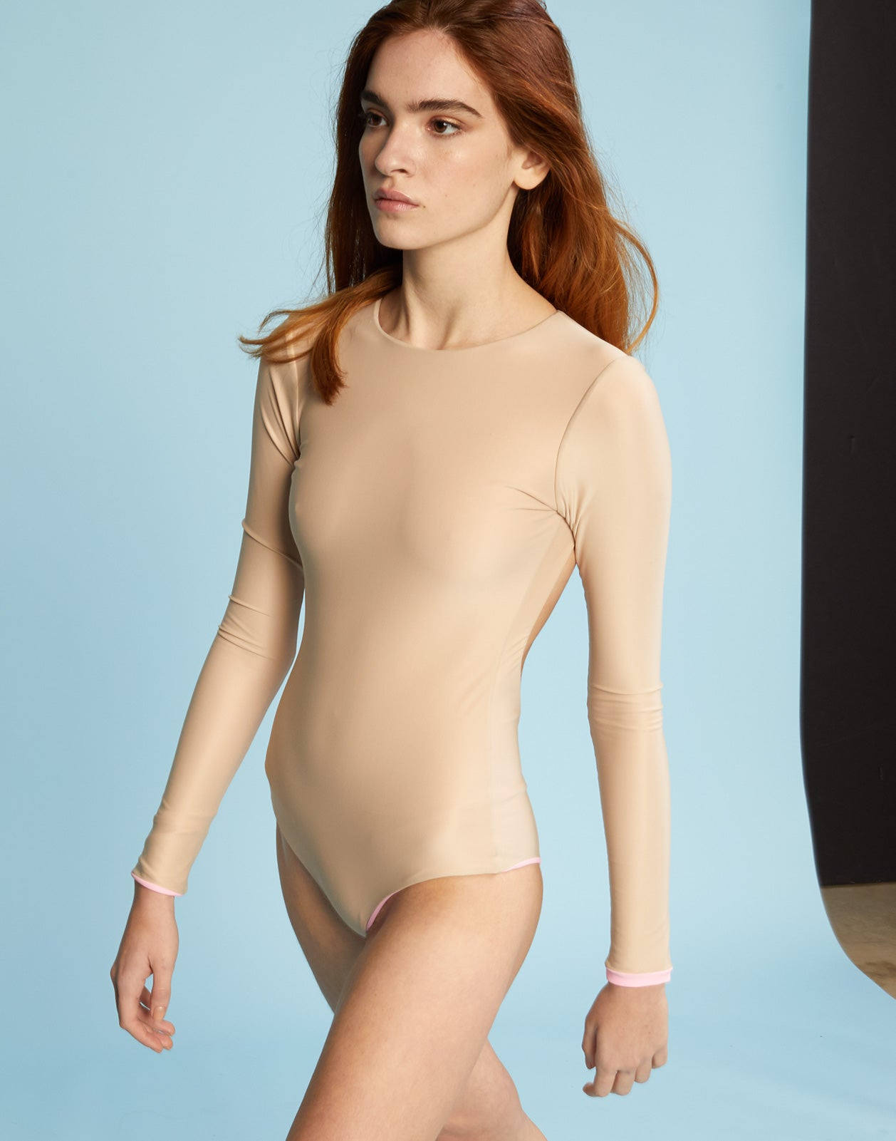 Model walking in solid two-tone surf suit with open back.
