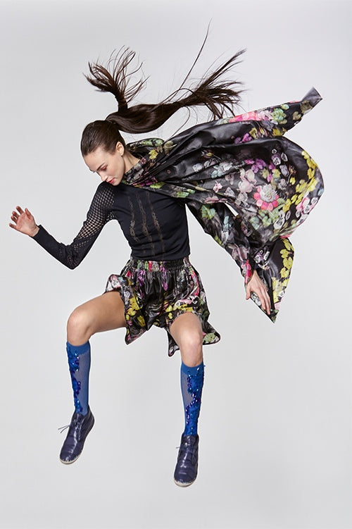 Cynthia Rowley Fall Fitness 2015 look 2 featuring dark floral print shorts and poncho, and black stretch long sleeve shirt with sheer cut outs