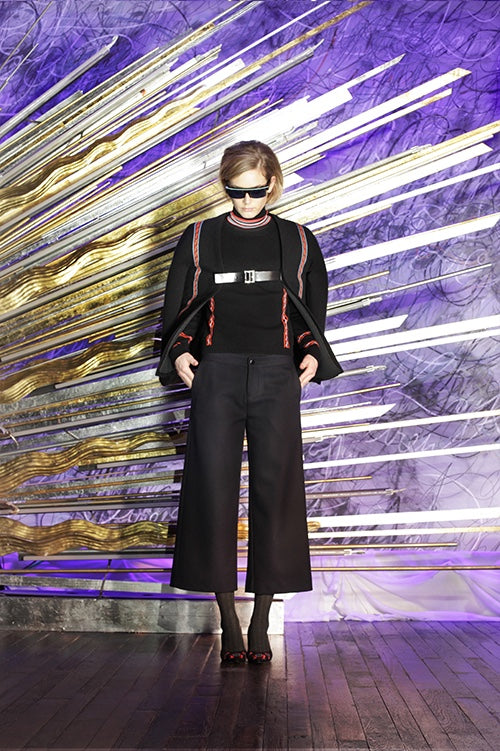 Cynthia Rowley Fall 2014 look 11 featuring a black long sleeve top with red black and white striped turtle neck and red applique on sleeves with a black coat with red applique stripe and buckle detail with black flared pants