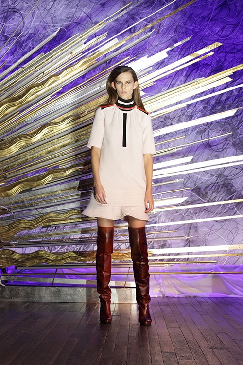 Cynthia Rowley Fall 2014 look 14 featuring a pale pink elbow length sleeve mini dress with black stripe on center front and black white red and orange stripe detail on shoulders and collar with ruffle hem