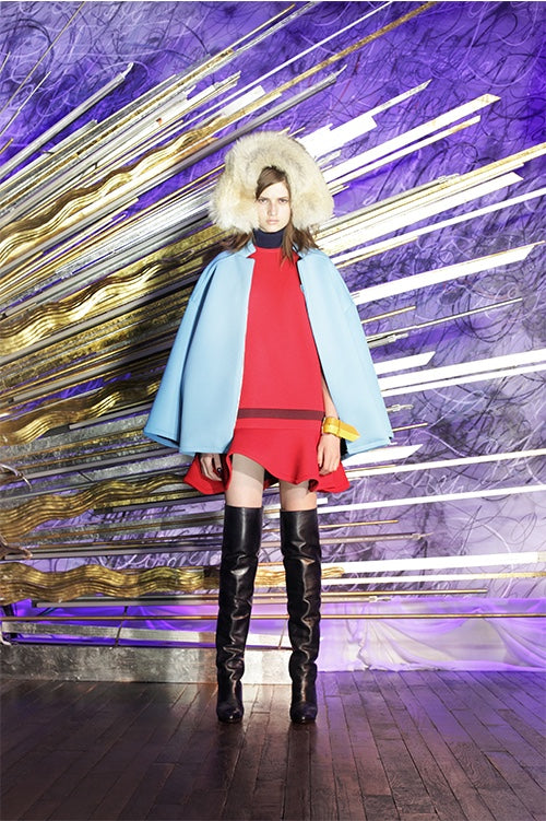 Cynthia Rowley Fall 2014 look 1 featuring a red dress with ruffle hem with a sky blue coat worn over the shoulder with knee high boots