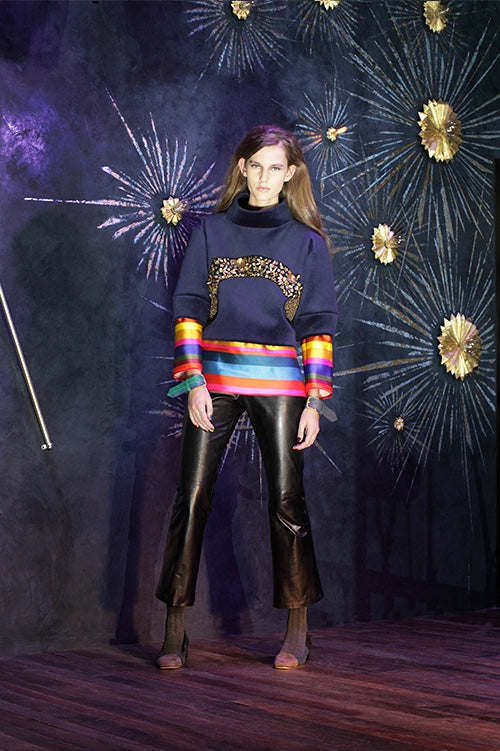 Cynthia Rowley Fall 2014 look 22 featuring a navy sweatshirt with embellished applique across the front with a layered rainbow stripe detail on hem and bottom of sleeves with black leather pants
