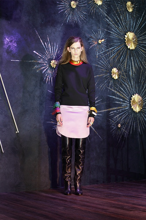 Cynthia Rowley Fall 2014 look 27 featuring a navy sweatshirt with yellow pink and blue buckles at the edge of the sleeves with a red neckline and a white mini skirt