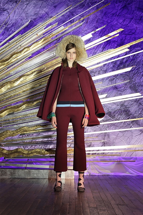 Cynthia Rowley Fall 2014 look 5 featuring a burgundy ankle length jumpsuit with navy and sky blue stripe detail at waist with a burgundy coat worn over the shoulders