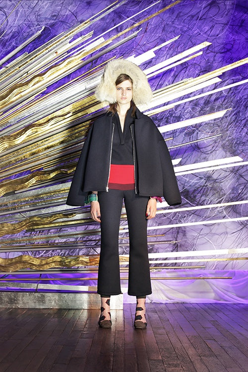 Cynthia Rowley Fall 2014 look 7 featuring a black v neck top with red stripe at the bottom with a black coat hanging and black ankle length pants