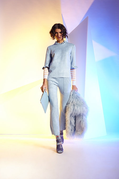 Cynthia Rowley Fall 2016 look 16 featuring baby blue bonded suede cargo flare pants and t-shirt with ruffles worn over a light blue and orange striped sweater