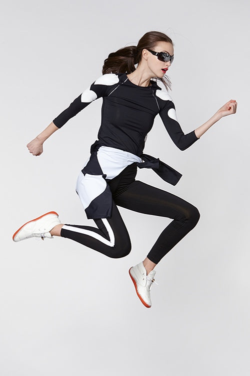Cynthia Rowley Fall Fitness 2015 look 13 featuring black leggings with white stripe and black long seen top with white hearts and color block wind breaker jacket ties around waist