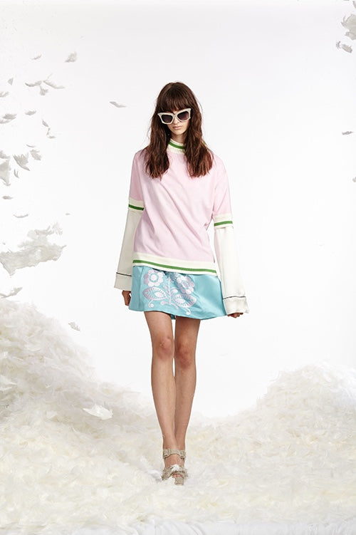 Cynthia Rowley Spring 2017 look 16 featuring an ice blue duchess satin mini skirt with white embroidery worn with a white silk pajama top and light pink and green striped terry cloth t-shirt