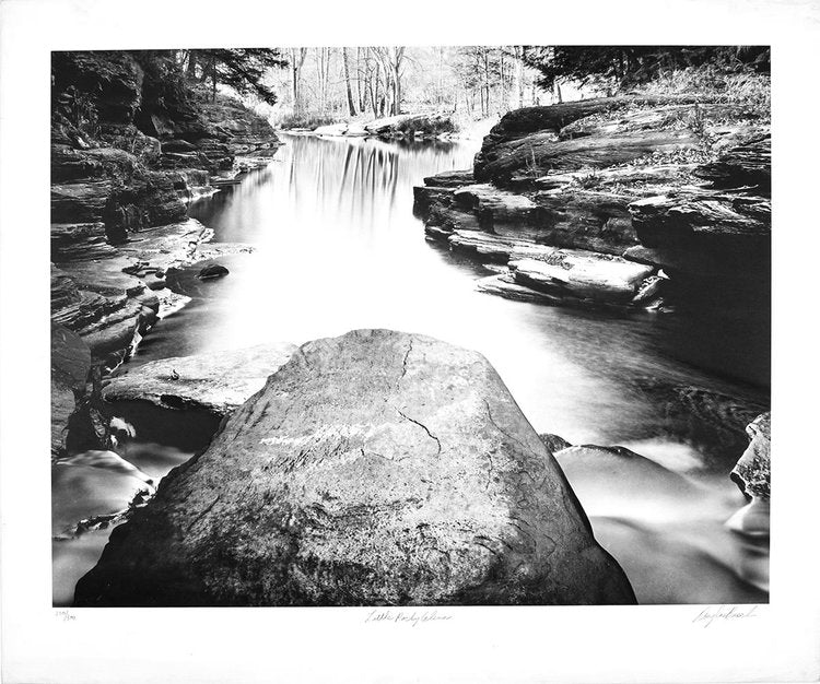 A black and white nature photograph of a rocky stream in the middle of the woods.