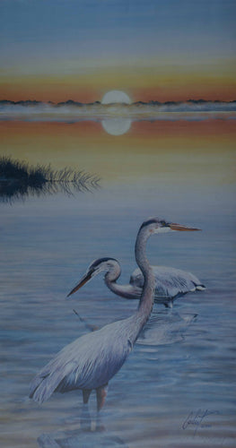 two Blue Herons with sunset over water scene with oranges blues