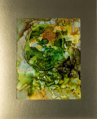 A beautiful green garden terrarium abstract in alcohol ink with golden yellows in a gold matt ready to be framed.
