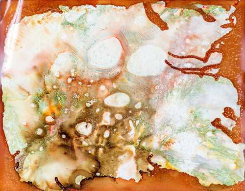 An abstract alcohol ink of a beach scene with browns, oranges, and greens.