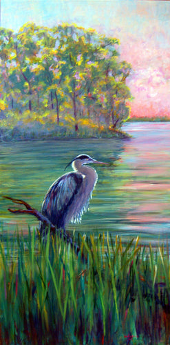 blue heron standing in wetlands marsh at dusk with beautiful pink sky
