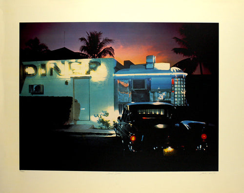 A vintage car sits in front of a diner while the sunsets. The car's headlights are on, shining on the restaurant as the pink and orange sky folds into darkness.
