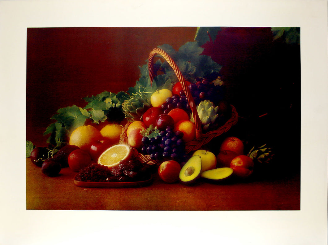A large wicker basket with an assortment of grapes, apples, mangoes, pears, oranges, and pomegranates.