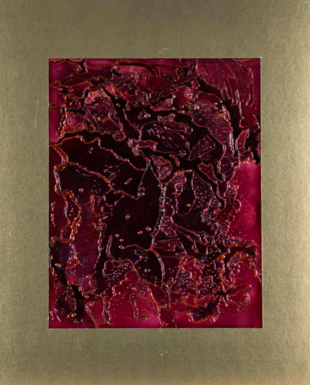 A red abstract alcohol ink in a gold matt, ready to be framed.