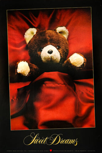 A cute Teddy bear is tucked into a bed in red satin sheets and pillows