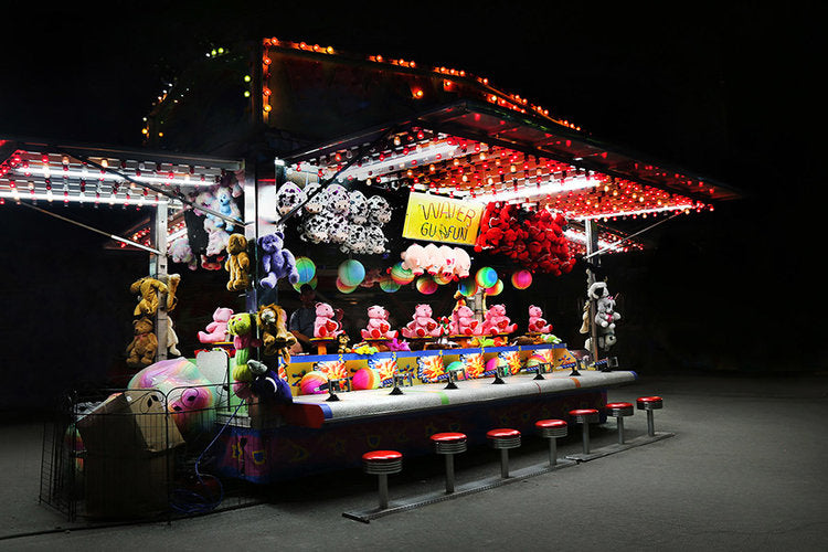 A colorful photograph of a carnival game at night. The toys illuminated by light contrast the darkness surrounding the fair game in an eerie and whimsical way.