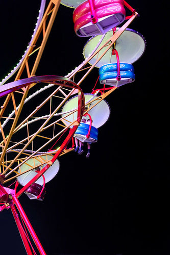 A colorful Ferris wheel at night with two passengers in a car enjoying the fair.