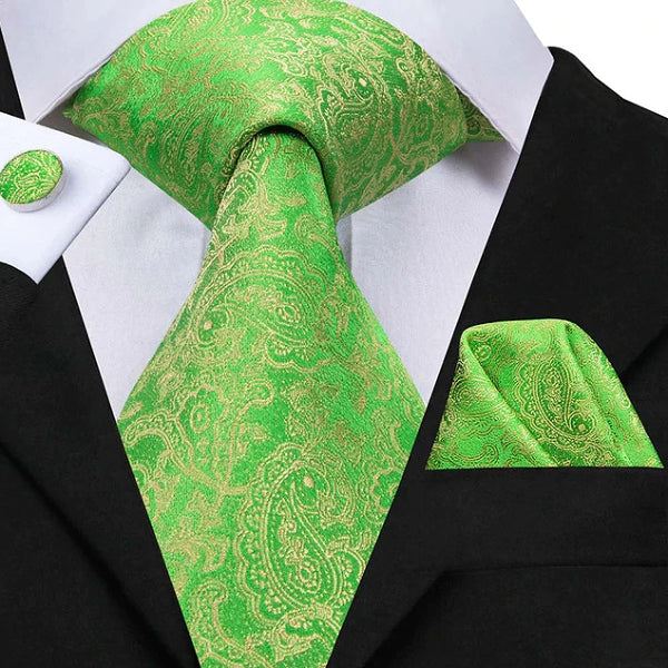 Green & gold paisley silk tie set displayed on a suit