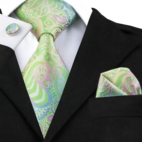Green gradient paisley silk tie set displayed on a suit