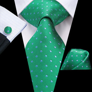 Green silk polka dot tie set with a matching pocket square and cufflinks on a suit