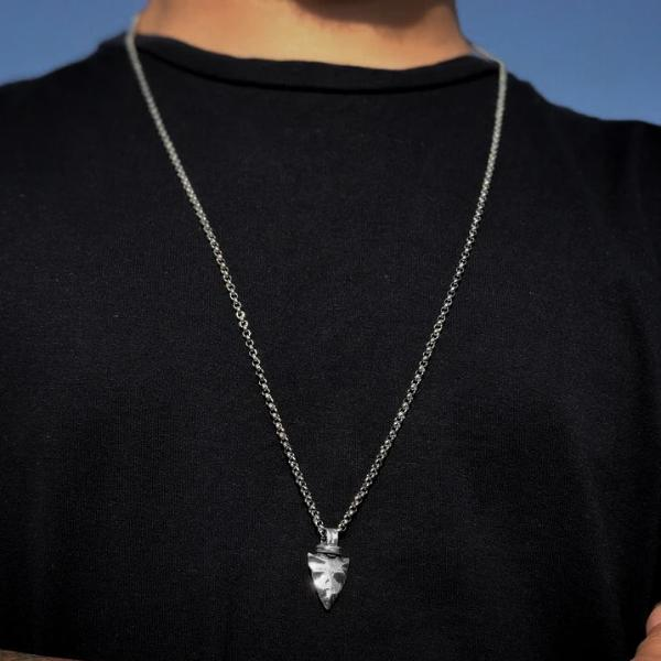 Man wearing a silver spearhead pendant necklace