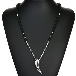 Black and silver wolf tooth necklace falls on the middle of the chest