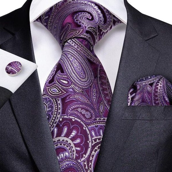 Man wearing a purple and ivory white paisley silk tie set with matching pocket square and cufflinks