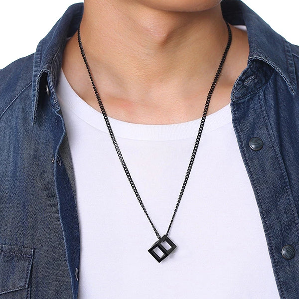 Man wearing a black cube pendant necklace for men