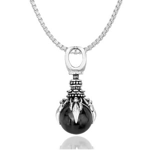 silver-toned oracle hand pendant with black crystal ball in it hanging from a chain